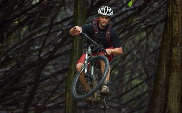 Wiggle staff member jumping confidently on his mountain bike facing camera