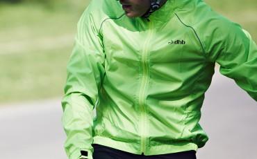 A cyclist wearing a green dhb waterproof jacket